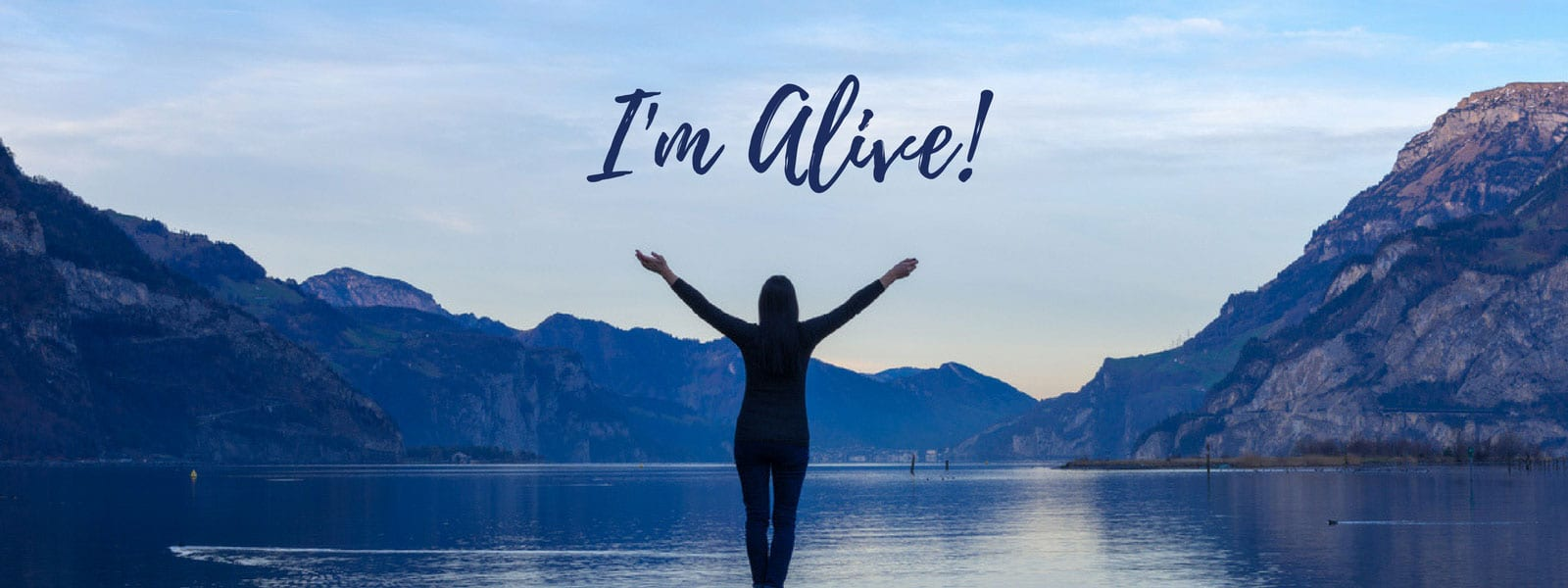 I'm Alive - Drug Alcohol treatment rehab story blog - Schick Shadel Hospital - Woman with arms raised on dock looking towards mountains and lake